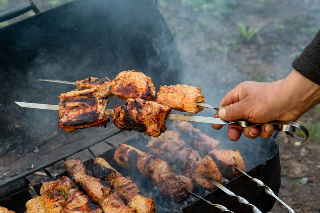 The male hand holds a skewer with barbecue. Summer picnic concept