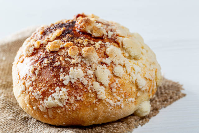 Baked bun with sugar crumbs on burlap