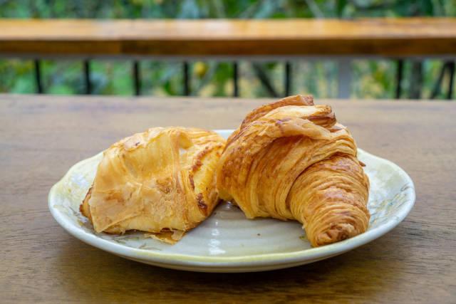 Buttercroissant und Blätterteig-Tasche auf einem weißen Teller Nahaufnahme