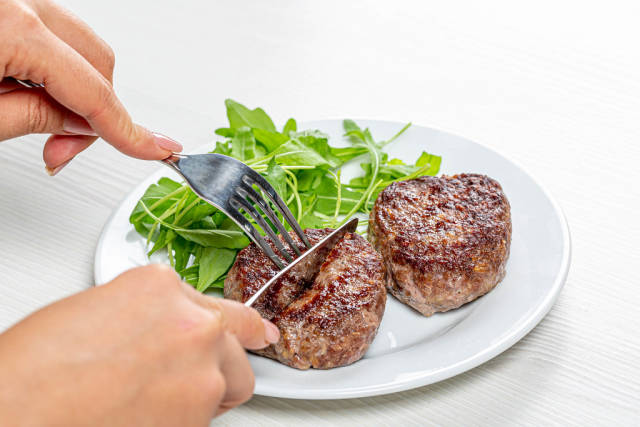 A woman with a knife and fork in her hands cuts a meat cutlet