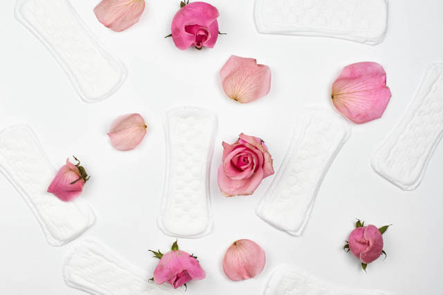 Background with womens hygiene products: loose panty liners, petals and roses on a white background