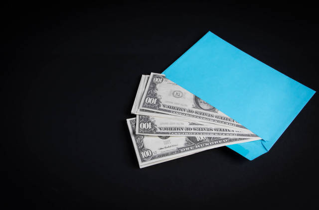 Blue envelope with money on black background