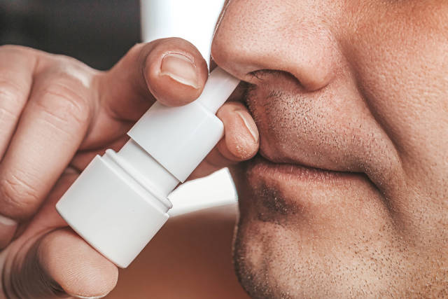 A man sprays medicine in his nose. Runny nose treatment concept