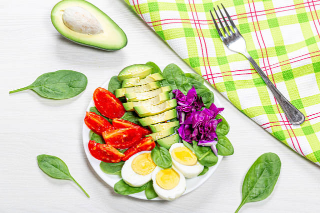 Top view healthy food background. Boiled eggs with fresh vegetables and spinach