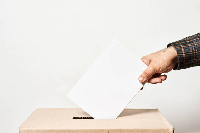 Election. Man throwing his vote into the ballot box
