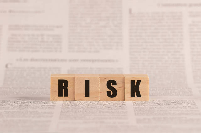 Risk written with cubes on a newspaper