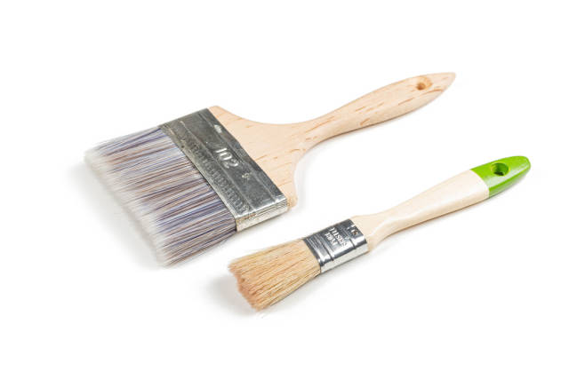 Two wooden paint brushes on a white background