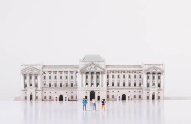 Miniature travelers stading in front of Buckingham Palace
