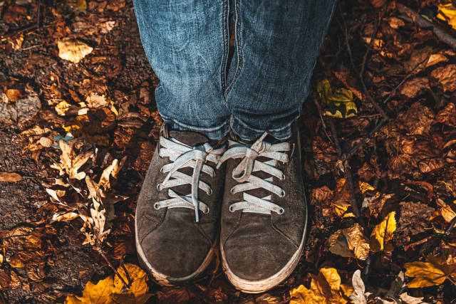 Autumn concept with womens feet in shoes on yellow dry leaves