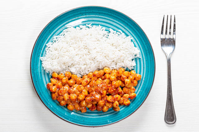 White rice and chickpeas in tomato sauce on white wooden background with fork. Top view