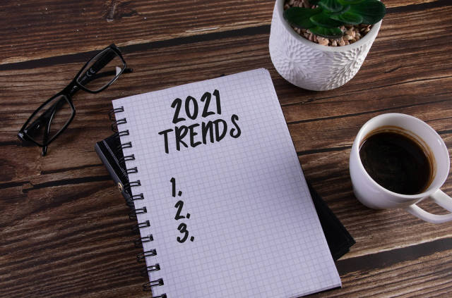 Open notebook with 2021 Trends text on wooden table