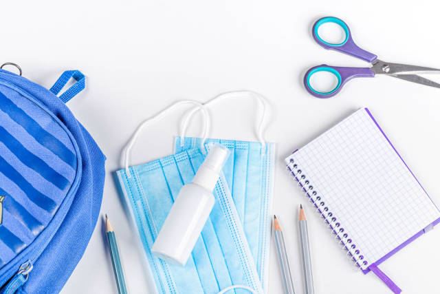 Blue briefcase, school items and personal protective equipment during quarantine