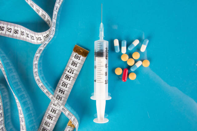 Medical syringe with pills and tape measure on blue background