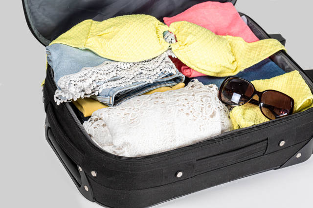 Open suitcase with clothes and personal things packed for travelling