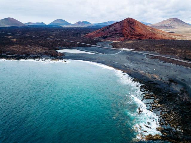 Red volcanic mountain in front of the ocean / Roter vulkanischer Berg vor dem Ozean