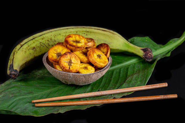 Raw and fried plantain on dark background with green leaf