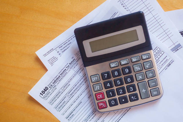 Tax form 1040 and a calculator. US tax form law document on a wooden desk. Business concept