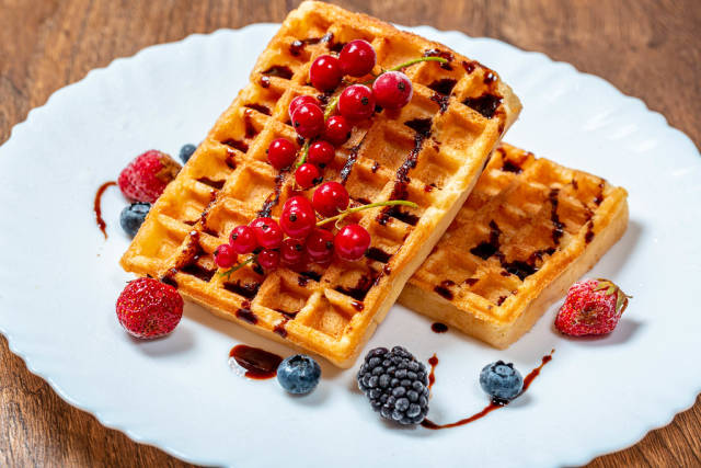 Two fried Belgian waffles with fresh fruit and chocolate syrup