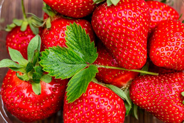 Fresh strawberry background with green leaves