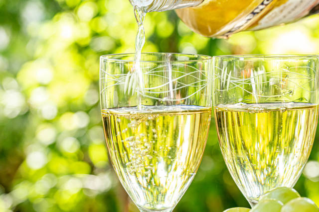 The glass is poured white wine on a blurred background of nature