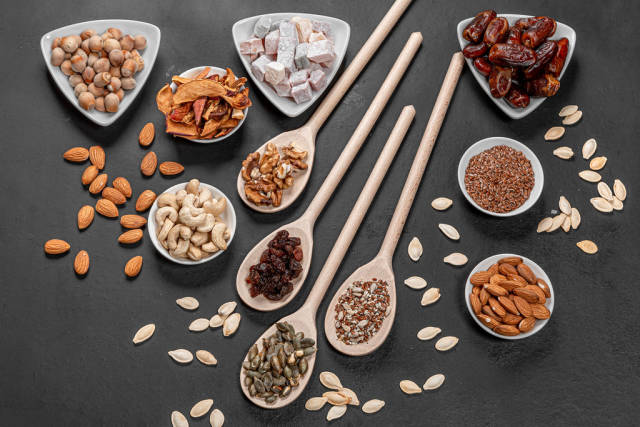 Top view dried fruits, nuts and seeds on a black background. Healthy food concept