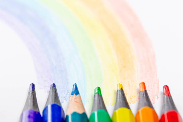 Close-up of colored pencils and a painted rainbow on a white background