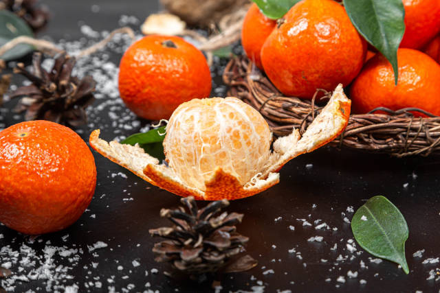 Peeled and whole tangerines on black background with leaves and snow