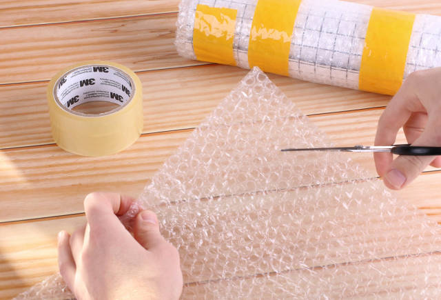 Man cutting bubble wrap with scissors