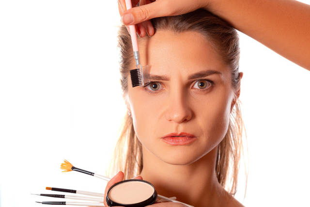 Makeup artist combing a womans eyebrows with a brush