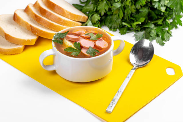 Spicy soup with carrots and sausages on the table with fresh parsley and slices of bread