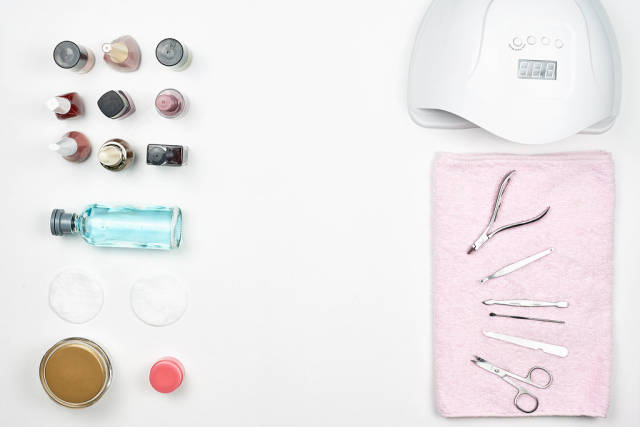 Nail polishes, UV lamp and various accessories and tools for manicure on white background