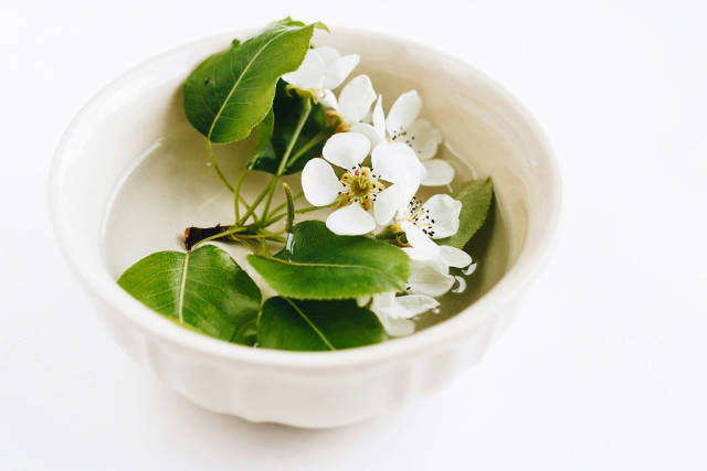 Spring flowers in a cup with water. Table decoration