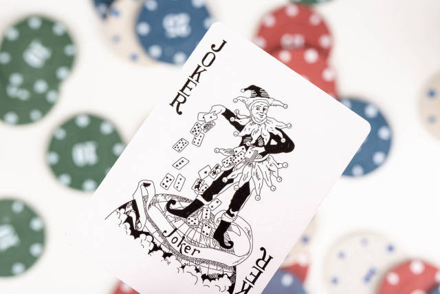 Close-up, black Joker on a blurry background of playing chips
