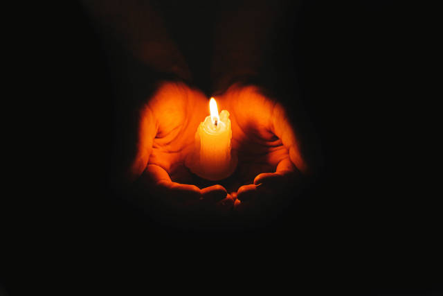 Candle flame glowing on a dark background in women hands. The concept of mourning, memory and hope
