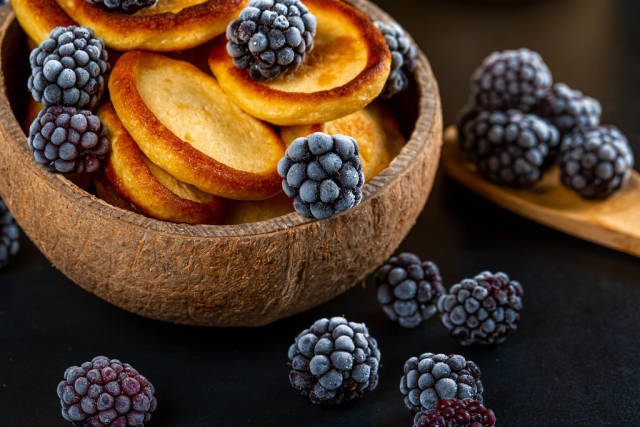 Pancakes in a wooden bowl with blackberries, close-up