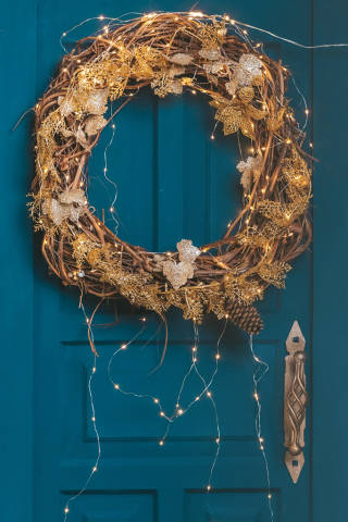 Christmas wreath with a luminous garland on a blue door