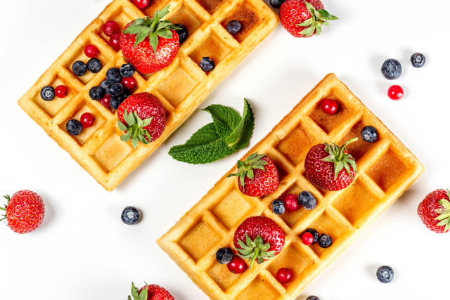 Top view, belgium waffles with fresh berries and mint leaves on a white background