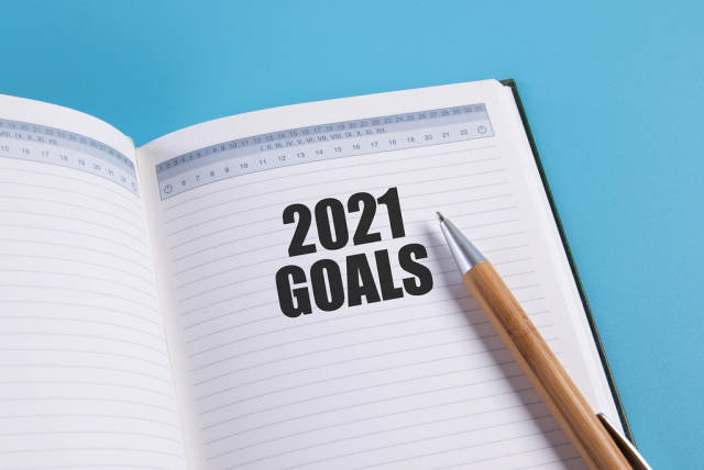 Open notebook with 2021 Goals text and pen on blue background