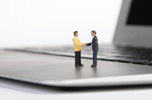 Businessman handshake on a laptop with white background