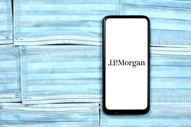 JPMorgan logo on smartphone screen over the face masks. Global company during coronavirus crisis