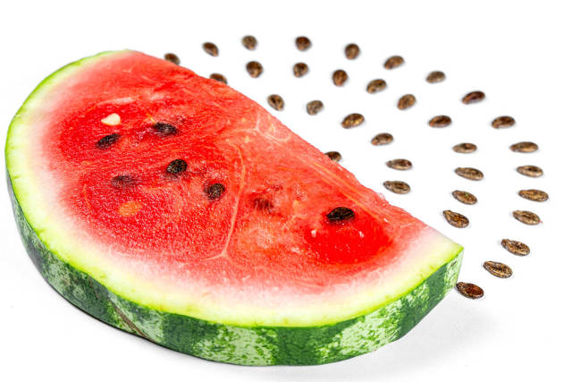 Slice of fresh watermelon and its seeds on white background