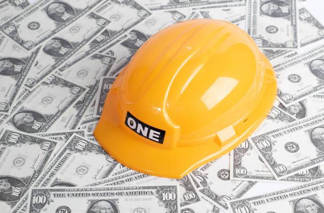 Gelber Schutzhelm für Bauarbeiter auf verteilten Banknoten symbolisiert Bauindustrie