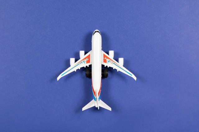 Flugzeug-Spielzeug vor einem Hintergrund aus blauem Papier