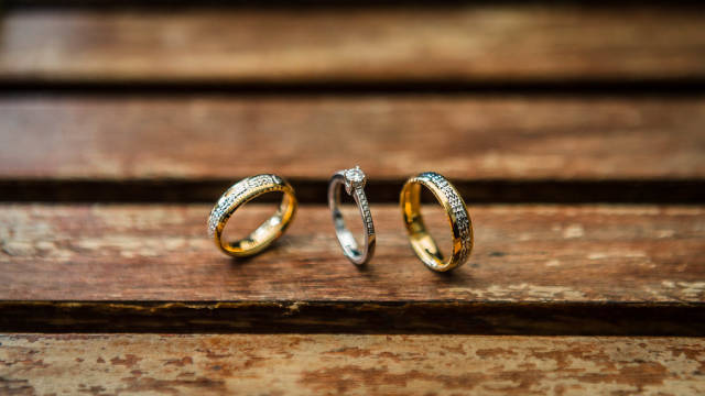 Close up shot of wedding rings on a wooden table