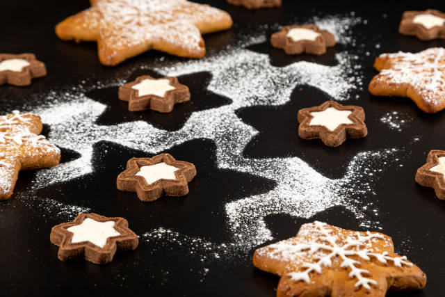 Christmas background with gingerbread, cookies and powdered sugar on black background