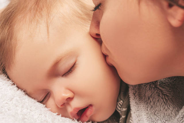 Close-up, mom kisses sleeping son
