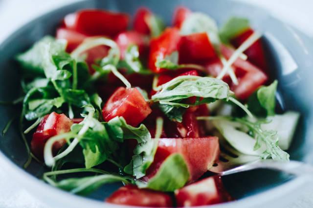 Nahaufnahme eines leichten Salats für den Sommer mit Tomaten und Rukola