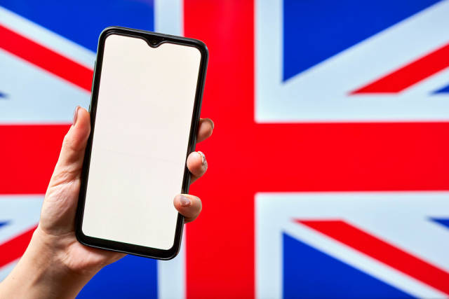 Hand holding a smartphone with a blank screen against the British flag