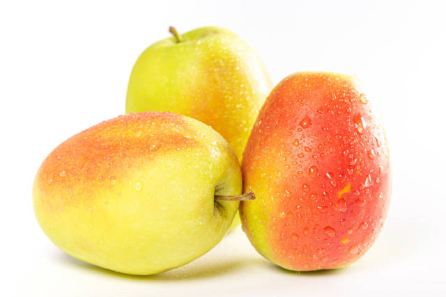 Three ripe apples on a white background
