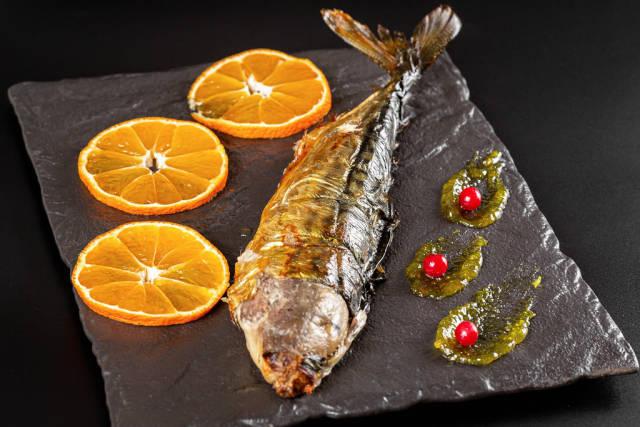Half-baked mackerel with orange slices, close-up